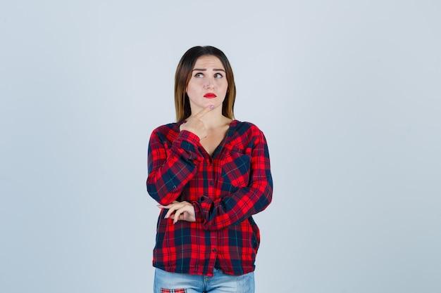 Jovem fêmea linda segurando o dedo no queixo em camisa casual e parecendo mal-humorada. vista frontal.