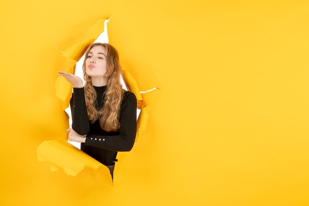 Jovem fêmea mandando beijos na parede amarela rasgada