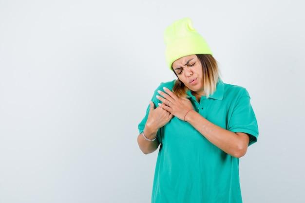 Jovem fêmea mantendo as mãos no peito em t-shirt polo, gorro e parecendo doloroso, vista frontal.