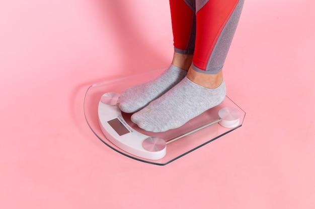 Jovem fêmea medindo seu peso na parede rosa exercício esporte treino atleta cintura beleza