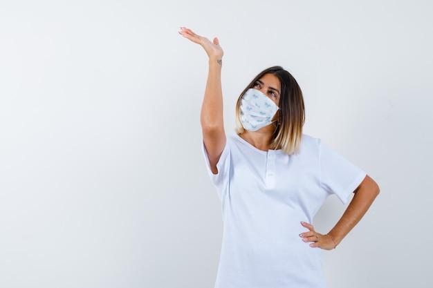 Jovem fêmea mostrando algo, mantendo a mão na cintura em t-shirt, máscara e olhando alegre, vista frontal.