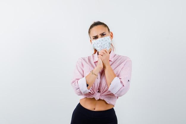 Jovem fêmea mostrando as mãos postas em um gesto de súplica na camisa, calça, máscara médica e olhando esperançosa, vista frontal.