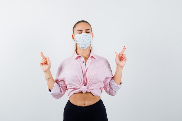 Jovem fêmea mostrando dedos cruzados na camisa, calça, máscara médica e olhando esperançosa, vista frontal.