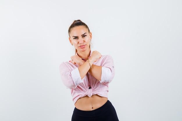 Jovem fêmea mostrando gesto de protesto em camisa casual, calças e olhando sério.
