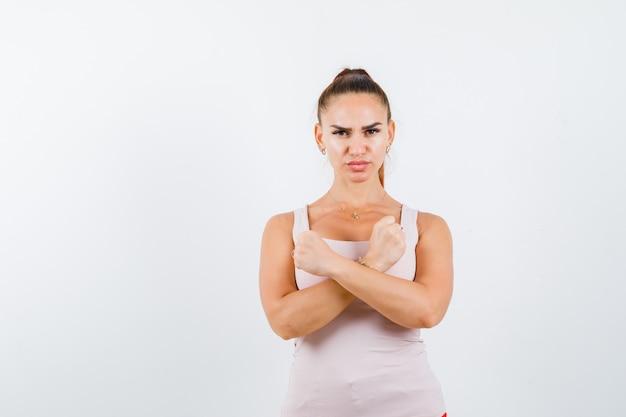 Jovem fêmea mostrando gesto de protesto na blusa branca e olhando séria, vista frontal.