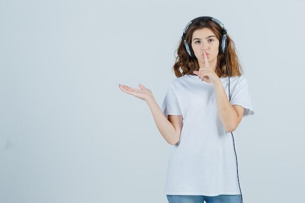 Jovem fêmea mostrando gesto de silêncio, espalhando a palma da mão para o lado em uma camiseta branca e parecendo sensata, vista frontal.