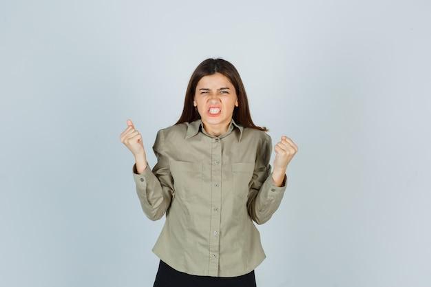 Jovem fêmea mostrando gesto de vencedor, cerrando os dentes na camisa, saia e parecendo com sorte. vista frontal.