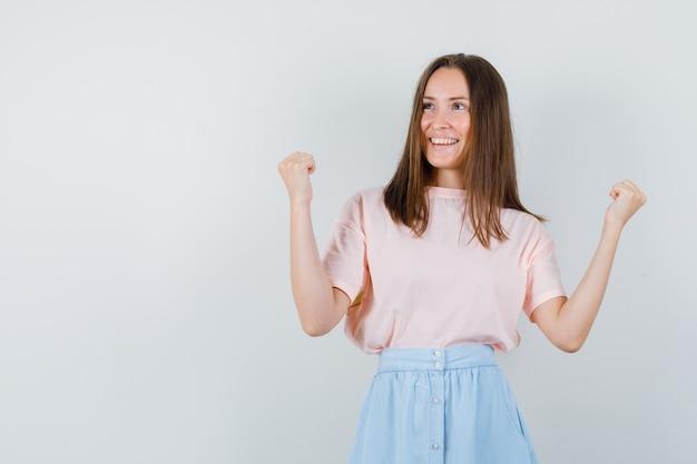 Jovem fêmea mostrando gesto de vencedor em t-shirt, saia e com sorte, vista frontal.