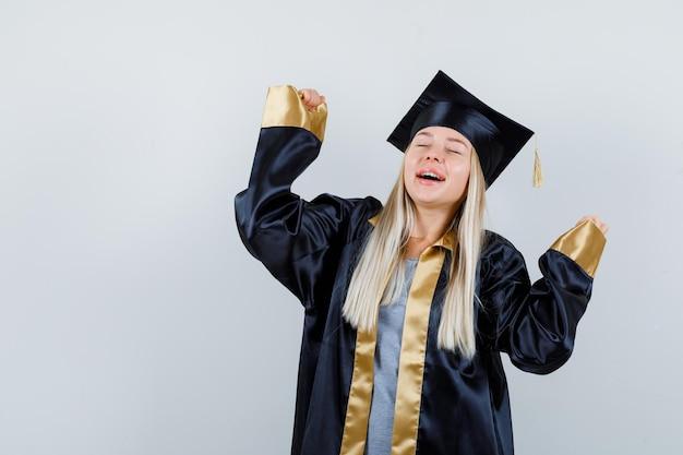 Jovem fêmea mostrando gesto de vencedor em uniforme de pós-graduação e parecendo feliz.