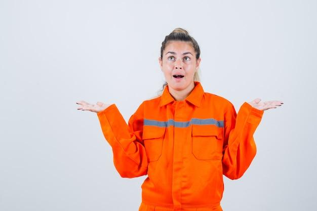 Jovem fêmea mostrando gesto idk em uniforme de trabalhador e parecendo confusa. vista frontal.