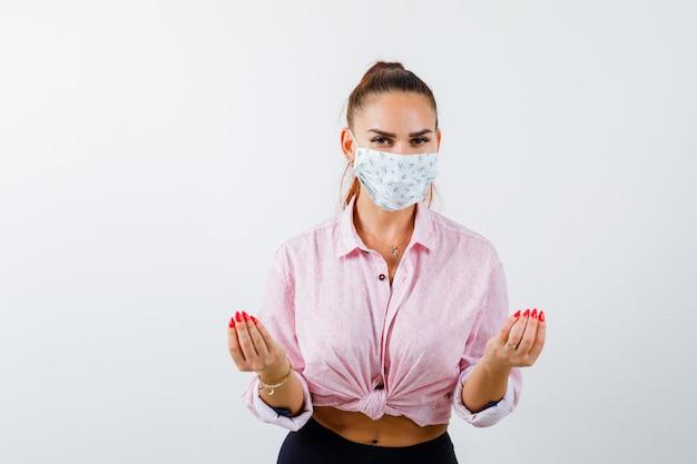 Jovem fêmea mostrando gesto italiano na camisa, calça, máscara médica e parecendo encantada. vista frontal.