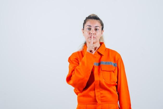 Jovem fêmea mostrando gesto silencioso em uniforme de trabalhador e olhando concentrada. vista frontal.