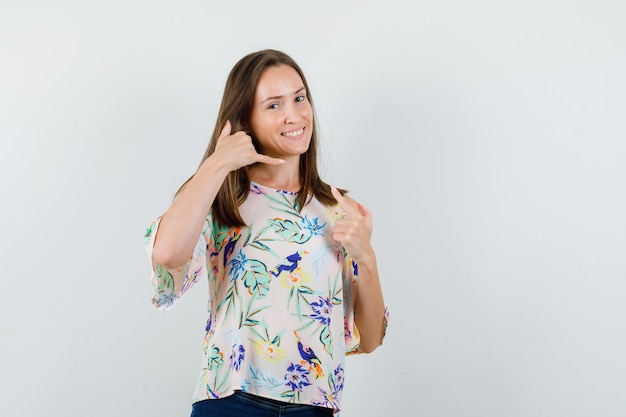 Jovem fêmea mostrando me chama de gesto em camisa, jeans e parecendo alegre. vista frontal.