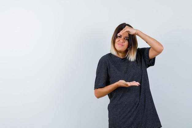 Jovem fêmea mostrando sinal de tamanho em vestido polo e parecendo confiante. vista frontal.