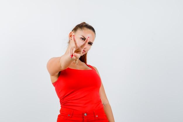 Jovem fêmea mostrando sinal de vitória em regata vermelha, calças e olhando com sorte, vista frontal.