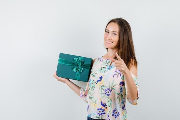 Jovem fêmea na camisa, segurando a caixa de presente e apontando para a câmera, vista frontal.