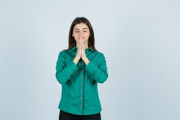 Jovem fêmea na camisa verde, de mãos dadas em gesto de oração e olhando esperançosa, vista frontal.