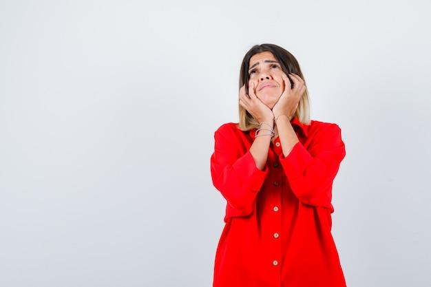 Jovem fêmea na camisa vermelha grande, apoiando o queixo nas mãos e olhando pensativa, vista frontal.