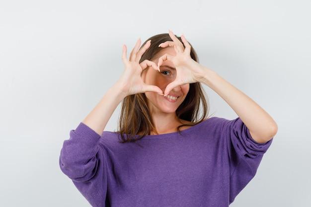 Jovem fêmea na camisa violeta, mostrando o gesto do coração e olhando alegre, vista frontal.