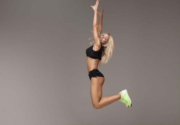 Jovem fêmea no agasalho pulando fazendo aeróbica cardio exercícios para perder peso e força de treinamento, desportista fazendo saltos queima calorias no treino de pilates, desfrutando de estilo de vida ativo l