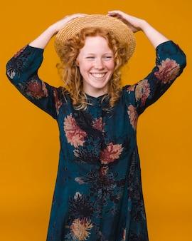 Jovem fêmea no chapéu com cabelo encaracolado vermelho sorrindo