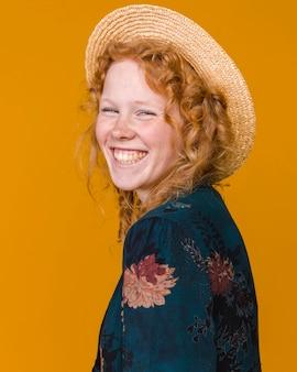Jovem fêmea no chapéu e com cabelo encaracolado sorrindo