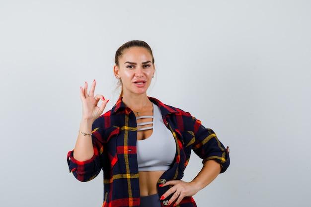 Jovem fêmea no top crop, camisa quadriculada, calças mostrando um gesto de ok, mantendo a mão no quadril e parecendo confiante, vista frontal.