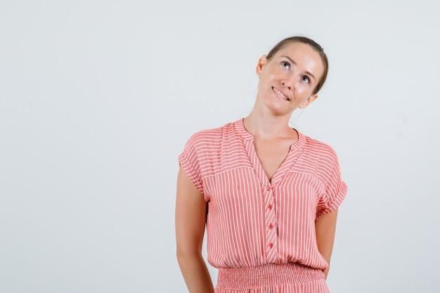 Jovem fêmea olhando com as mãos nas costas em um vestido listrado e parecendo um sonho, vista frontal.