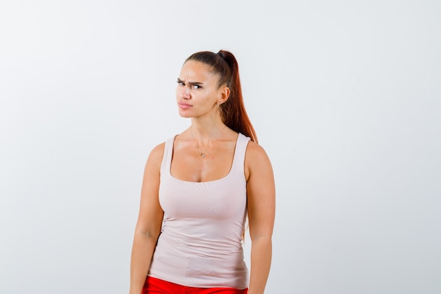 Jovem fêmea olhando para a câmera enquanto carranca na blusa branca, calças e olhando descontente, vista frontal.