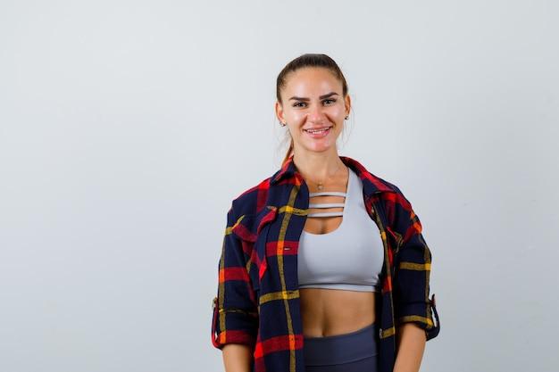 Jovem fêmea olhando para a câmera no top crop, camisa quadriculada, calças e parecendo feliz, vista frontal.