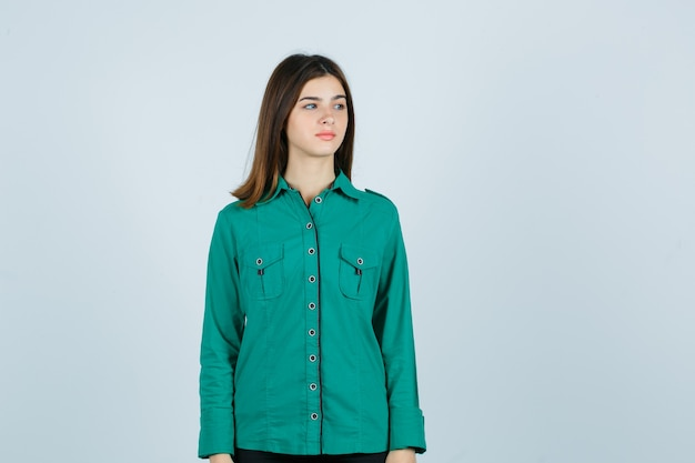 Jovem fêmea olhando para longe em uma camisa verde e parecendo triste. vista frontal.
