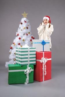 Jovem fêmea perto de presentes de natal em cinza