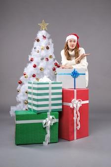 Jovem fêmea perto de presentes de natal no chão cinza feriado de presente de natal