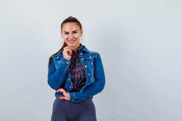 Jovem fêmea posando em pé com camisa quadriculada, jaqueta, calça e olhando alegre, vista frontal.