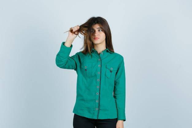 Jovem fêmea puxando o cabelo na camisa verde e parecendo decepcionada, vista frontal.