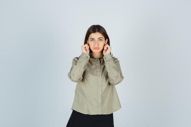 Jovem fêmea puxando para baixo os lóbulos das orelhas, curvando o lábio inferior na camisa