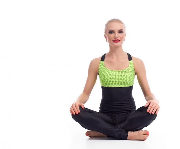 Jovem fêmea realizando lótus asana meditando fazendo yoga