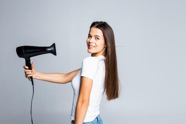 Jovem fêmea, secando o cabelo moreno bonito com secador de cabelo isolado no branco