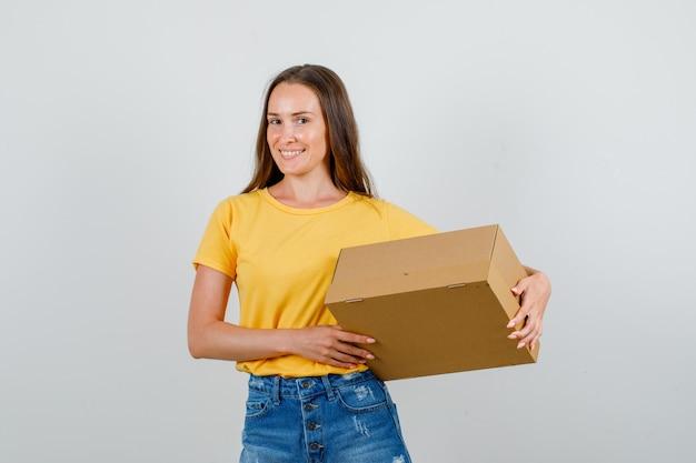 Jovem fêmea segurando a caixa de papelão e sorrindo em t-shirt, vista frontal de shorts.