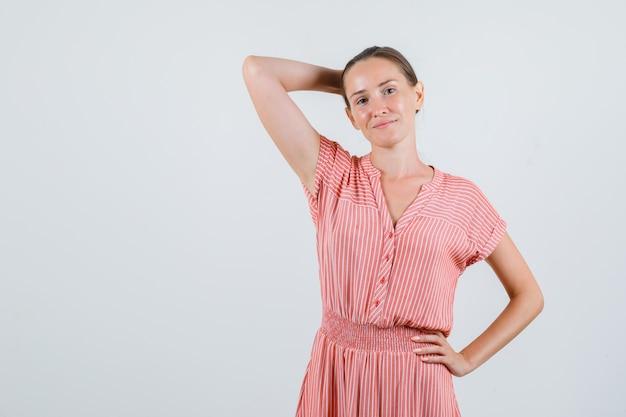 Jovem fêmea segurando a mão atrás da cabeça em vestido listrado, vista frontal.