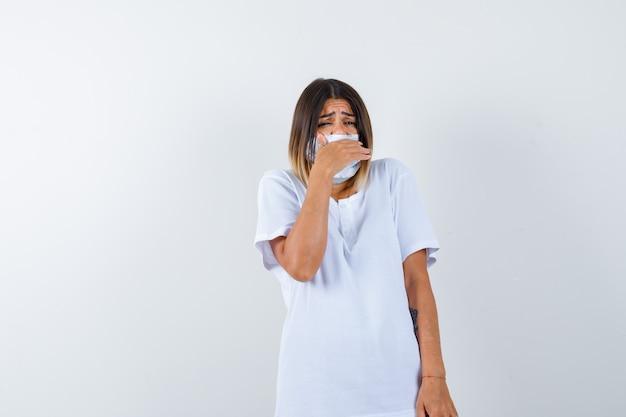 Jovem fêmea segurando a mão na boca em t-shirt, máscara e olhando com medo, vista frontal.