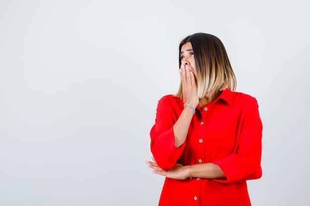 Jovem fêmea segurando a mão na boca em uma camisa vermelha grande e olhando perplexa, vista frontal.