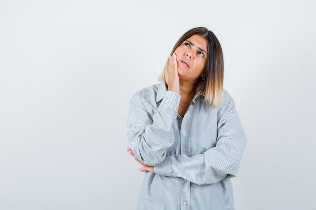 Jovem fêmea segurando a mão na bochecha em uma camisa grande e olhando pensativa, vista frontal.