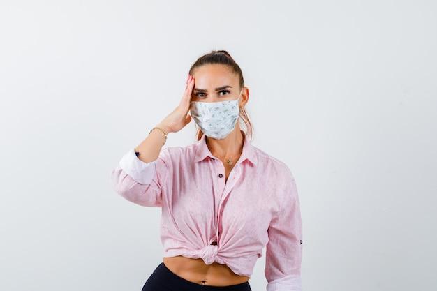 Jovem fêmea segurando a mão na cabeça em camisa, calça, máscara médica e olhando pensativa, vista frontal.