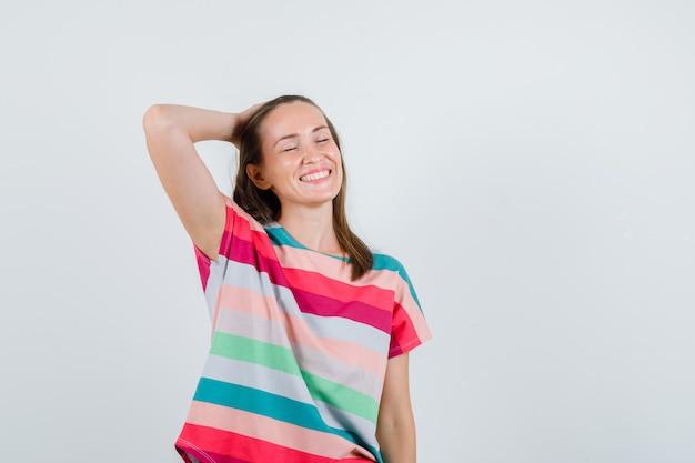 Jovem fêmea segurando a mão na cabeça em t-shirt e olhando feliz, vista frontal.