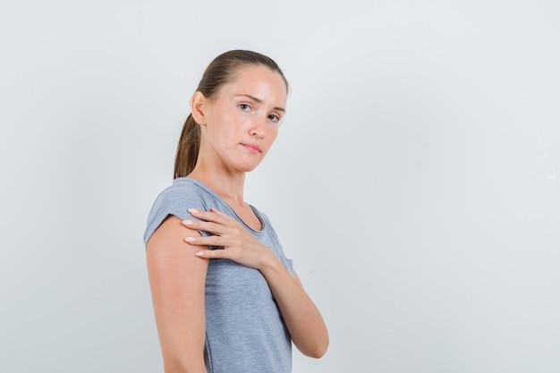 Jovem fêmea segurando a mão perto do peito em t-shirt cinza e olhando sério. vista frontal.