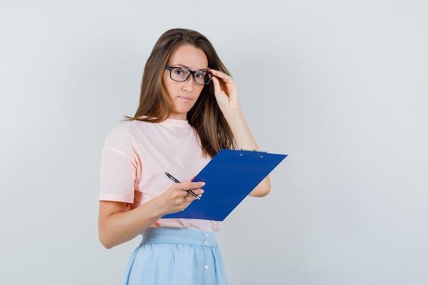 Jovem fêmea segurando a prancheta e uma caneta em t-shirt, saia e olhando cuidadoso. vista frontal.