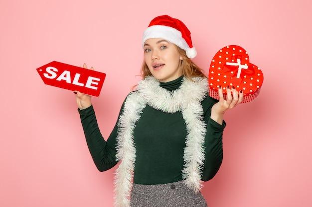 Jovem fêmea segurando a venda vermelha escrita e presente na parede rosa natal ano novo compra emoção feriado cor