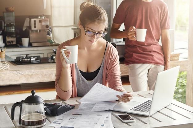 Jovem fêmea segurando a xícara de chá em uma mão, olhando com expressão séria no papel em outra