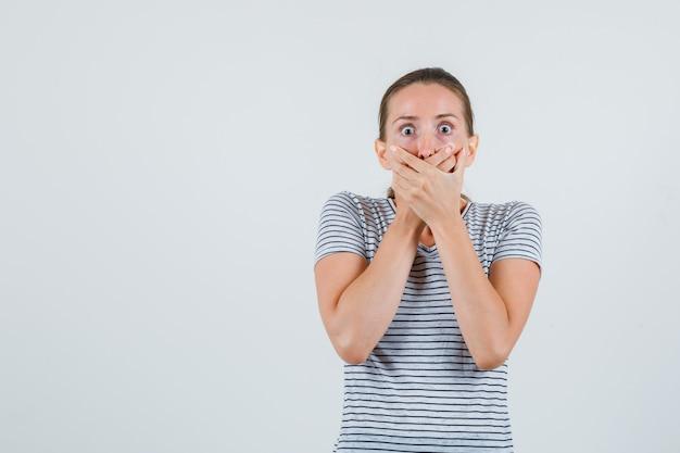 Jovem fêmea segurando as mãos na boca em uma camiseta listrada e parecendo assustada. vista frontal.